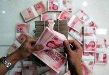 BEIJING - JULY 22: (CHINA OUT) A clerk counts stacks of Chinese yuan at a bank on July 22, 2005 in Beijing, China. The People's Bank of China, the central bank, announced on July 21 to scrap the yuan's decade-old peg to the U.S. dollar, and in stead phase in a flexible mechanism of the yuan exchange rates. The exchange rate of yuan vs U.S. dollar was announced at 8.11 vs 1 on July 22. (Photo by China Photos/Getty Images)