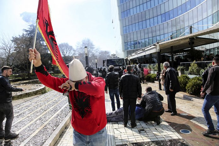 A protester holding an Albanian flag tries to escape from tear gas during an anti-government rally in Tirana, Albania, on Saturday, March 16, 2019. Albanian opposition supporters clashed with police while trying to storm the parliament building Saturday in a protest against the government which they accuse of being corrupt and linked to organized crime. (AP Photo/Visar Kryeziu)