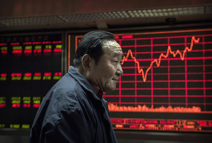 BEIJING, CHINA - JANUARY 22: An elderly Chinese day trader stands in front of stock tickers on a board at a brokerage firm on January 22, 2015 in Beijing, China. China's economic growth has slowed to its weakest point in years to 7.4 percent. While its growth is still stronger than most world economies, China announced Tuesday a strategy to encourage domestic consumption and investment including retail spending in an effort to boost growth. (Photo by Kevin Frayer/Getty Images)