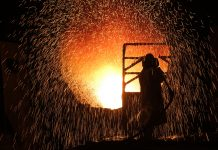 SALZGITTER, GERMANY - MARCH 05: Sparks fly as a worker in a heat resistant suit cleans the inside of a ladle used for transporting molten metal at the Salzgitter AG steelworks on March 05, 2019 in Salzgitter, Germany. Salzgitter produces a wide variety of steel products, including galvanized flat steel used for cars and appliances. (Photo by Sean Gallup/Getty Images)