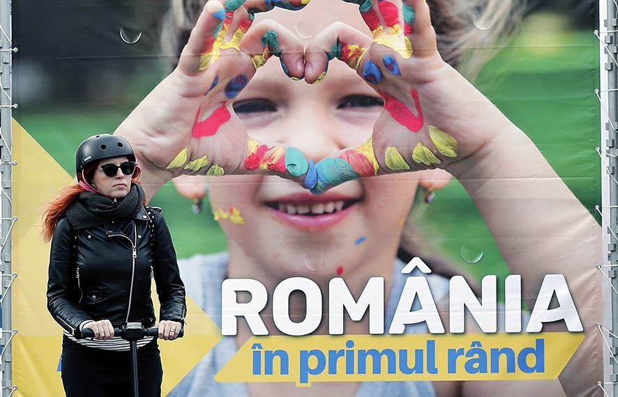 epa07450561 An young Romanian woman rides her electric scooter in front of a banner campaigning for European parliamentary elections on behalf of PNL (National Liberal Party), in Bucharest, Romania, 20 March 2019. The banner reads: 'Romania first'. European Union parliamentary elections will take place from 23 until 26 May 2019. EPA/ROBERT GHEMENT