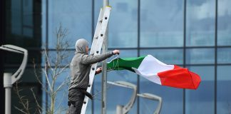 LIVERPOOL, ENGLAND - APRIL 26: A man ties an Italian flag to a lampost outside Alder Hey Children's Hospital on April 26, 2018 in Liverpool, England. Tom Evans the father of seriously ill, 23-month-old, Alfie Evans has said he will meet with doctors to discuss taking his son home. The Court of Appeal has upheld a ruling preventing Alfie's parents taking their son for treatment to Italy. (Photo by Anthony Devlin/Getty Images)