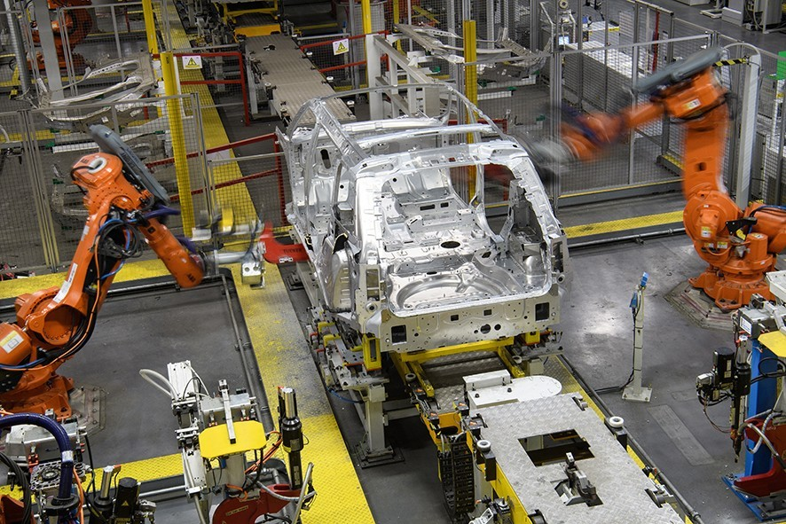 """SOLIHULL, ENGLAND - MARCH 06: Robotic systems work on the chassis of a car during an automated stage of production at the Jaguar Land Rover factory on March 1, 2017 in Solihull, England. The company has pledged it's 'heart and soul' to production in the UK after producing the new """"Velar"""" model for global sale, at their Solihull factory. (Photo by Leon Neal/Getty Images)"""