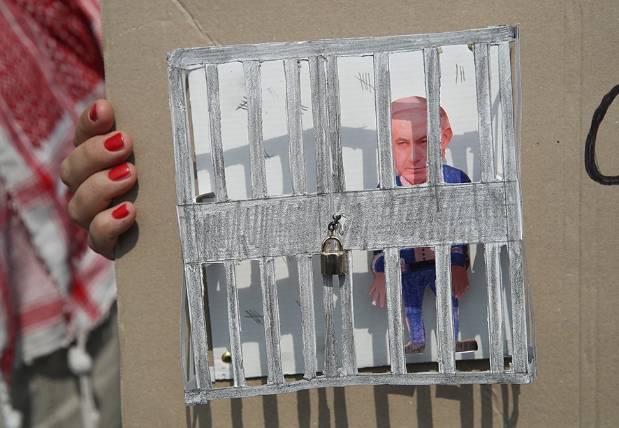 BERLIN, GERMANY - JUNE 04:  An effigy of Israeli Prime Minister Benjamin Netanyahu stands in a paper prison on a protester's sign during a demonstration near the Chancellery prior to the arrival of Netanyahu on June 4, 2018 in Berlin, Germany. Netanyahu, who is meeting today with Chancellor Angela Merkel, is travelling this week to Berlin, Paris and London in an effort to convince European leaders to adopt a more hardline approach towards Iran.  (Photo by Sean Gallup/Getty Images)