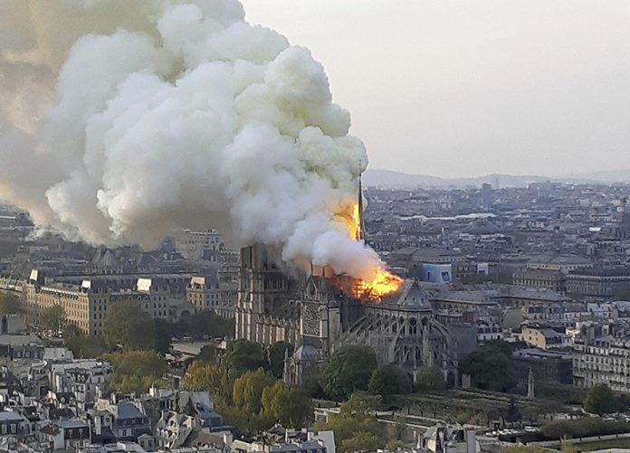 In this image made available on Tuesday April 16, 2019 flames and smoke rise from the blaze at Notre Dame cathedral in Paris, Monday, April 15, 2019. An inferno that raged through Notre Dame Cathedral for more than 12 hours destroyed its spire and its roof but spared its twin medieval bell towers, and a frantic rescue effort saved the monument's