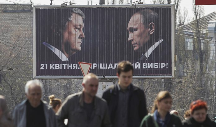 epa07496043 Ukrainians pass by a billboard of acting President and Presidential candidate Petro Poroshenko depictured face to face with Russian President Vladimir Putin in Kiev, Ukraine, 10 April 2019. The run-off vote of the Presidential elections will take place in Ukraine on 21 April 2019. EPA/STEPAN FRANKO