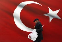 A man walks by a giant Turkish flag in Ankara, Turkey, Sunday, March 31, 2019. Turkish citizens have begun casting votes in municipal elections for mayors, local assembly representatives and neighborhood or village administrators that are seen as a barometer of Erdogan's popularity amid a sharp economic downturn. (AP Photo/Ali Unal)