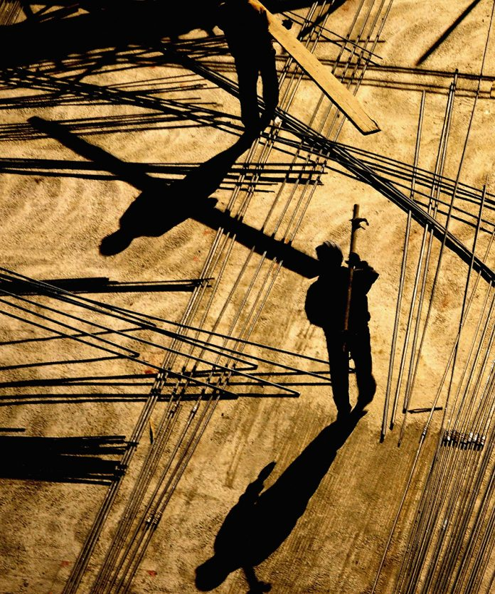 BEIJING, CHINA - MARCH 19: Chinese labourers work at a construction site in the evening under floodlights on March 19, 2005 in Beijing, China. Acting to cool the sizzling property market, China's central bank tightened mortgage lending rules to raise the cost of borrowing for home loans.