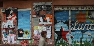BERLIN, GERMANY - JUNE 21: A woman walks past the radical left-wing and anarchist Die Lunte center in the Schiller-kietz neighborhood in Neukoelln district on June 21, 2012 in Berlin, Germany. Five unknown assailants smashed windows and splashed red paint on the facade of the nearby Schiller Backstube bakery and Schillerbar, and according to media reports a left-wing group protesting rising rents and gentrification of the neighborhood has claimed responsibility. Gentrification, whether real or perceived, of neighborhoods like Neukoelln, Kreuzberg and Friedrichshain has led to threats and violent protests from radical left-wing groups. Berlin, in stark contrast to other European capitals like London and Paris, has long had a very affordable housing market, though prices in central districts have risen dramatically in the last two years. (Photo by Sean Gallup/Getty Images)