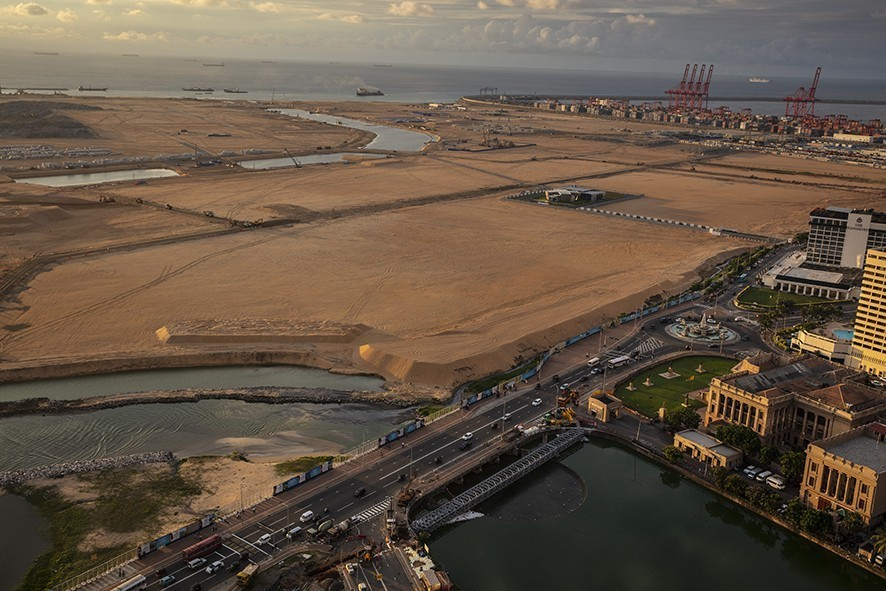 """COLOMBO, SRI LANKA - NOVEMBER 20: Built on land reclaimed from the Indian Ocean and funded with $1.4billion in Chinese investment, the Colombo Port City project is seen jutting out into the ocean that will eventually be 65 million cubic meters of sand on November 8, 2018 in Colombo, Sri Lanka. In just a few years Port City will be the site of tall glass skyscrapers, a busy financial district, hospitals, hotels and even a theme park. As the political crisis escalates in Sri Lanka, former President Mahinda Rajapaksa""""u2019s return to power in late October has been watched with increasing concern by countries including the U.S., China and India. The re-entry of Rajapaksa could and raise the influence from Beijing and alter the power dynamics around the Indian Ocean. During Rajapaksa""""u2019s 2005-2015 presidency, Sri Lanka saw an influx of Chinese investment and economic support since he relied heavily on China for economic support, military equipment and political cover. While ousted Prime Minister Ranil Wickremesinghe sought to balance relations with New Delhi and Beijing, Rajapaksa made clear his willingness to accept Chinese money even in the face of unreasonable terms while reports from the Central Bank estimated the debt owed to China could be as much as $5 billion and growing every year. Chinese investments paid for a new port, a new airport and new railway on Sri Lanka""""u2019s southern coast, among other projects in Colombo, which forced the government to sell strategic assets to Beijing, such as the Hambantota port, when it wasn't able to meet liabilities. For China, the relation with Sri Lanka ties back thousands of years when it was a stop along the old Silk Road trade routes, as it is now known to be a critical link for its Belt and Road Initiative, which aims to expand trade across 65 countries from the South Pacific through Asia to Africa and Europe.  (Photo by Paula Bronstein/Getty Images)"""