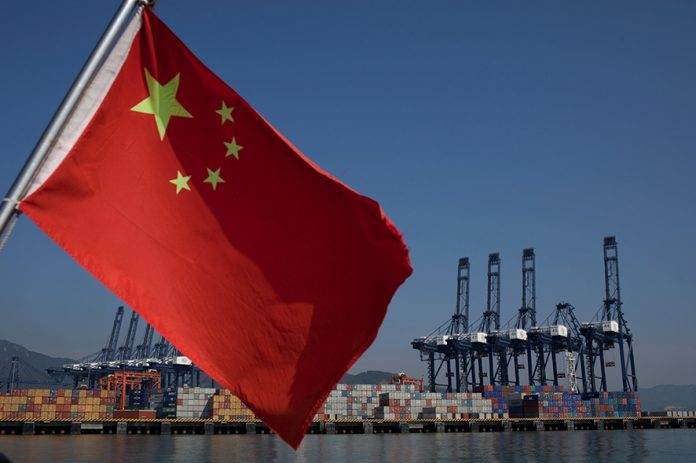 SHENZHEN, CHINA - NOVEMBER 28: A Chinese flag attached to the back of a boat flaps in the wind as cargo containers sit on the dock of Shenzhen Port on November 28, 2010 in Shenzhen, China. According to the US Commercial Service, Shenzhen is one of the fastest growing cities in the world. Home of the Shenzhen Stock Exchange and the headquarters of numerous technology companies, the now bustling former fishing village is considered southern China's major financial centre. (Photo by Daniel Berehulak/Getty Images)