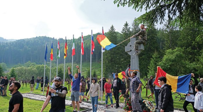 epa07632204 Romanian people wave Romanian flags at the International Heroes Cemetery in Valea Uzului (or Uzvolgye in Hungarian language), Harghita County, Romania, 06 June 2019 (issued 07 June 2019). Thousands of Romanian protesters broke through the police line to attend an orthodox dedication ceremony of a Romanian monument erected by the municipality of eastern Romanian town Darmanesti at the WWI memorial site. At the end of April 2019, Romanian tombstones were placed behind the Hungarian wooden crosses, which caused tensions between two nations. EPA/NANDOR VERES HUNGARY OUT
