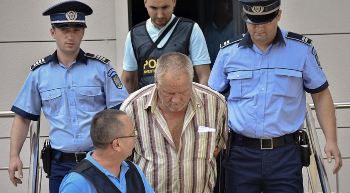 Police officers escort Gheorghe Dinca, the suspect in the case of rape and murder of a 15 year-old girl, from a court in Craiova, southern Romania, Saturday, July 27, 2019. Thousands of people took part Saturday evening in Bucharest in a march protesting the handling of the case, blaming Romanian officials for negligence, incompetence and a lack of empathy. (AP Photo/Bogdan Danescu)
