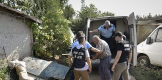 Police officers escort Gheorghe Dinca, the suspect in the case of rape and murder of a 15 year-old girl, to his home in Caracal, southern Romania, for further investigations, Saturday, July 27, 2019. Thousands of people took part Saturday evening in Bucharest in a march protesting the handling of the case, blaming Romanian officials for negligence, incompetence and a lack of empathy. (AP Photo/Bogdan Danescu)