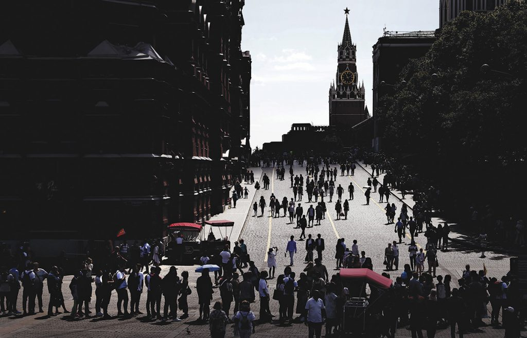 epa07689092 The sun shines through the clouds on Kremlevskiy Proyezd street as people walk in front of the Kremlin (background C) in downtown Moscow, Russia, 02 July 2019. EPA/MAXIM SHIPENKOV