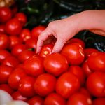 MEXICO CITY, MEXICO - MAY 09: A woman picks a tomato at a market on Matías Romero street on May 9, 2019 in Mexico City, Mexico. On May 7 the United States imposed a 17.5% tariff on tomatoes of Mexican origin after a breakdown of a 22 year agreement. (Photo by Manuel Velasquez/Getty Images)