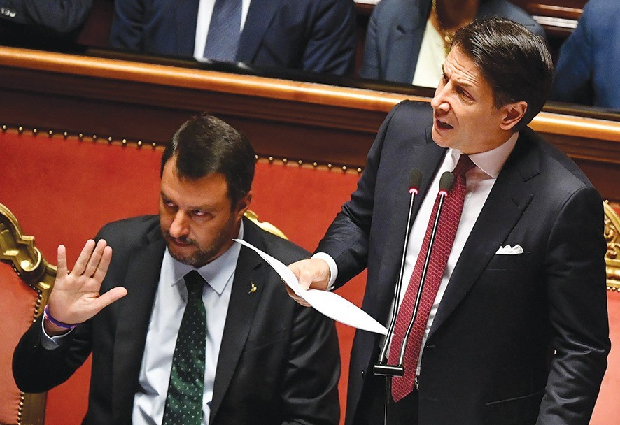 epa07782272 Italian Prime Minister Giuseppe Conte (R) is flanked by Deputy Prime Ministers Matteo Salvini (L) as he addresses the Senate in Rome, Italy, 20 August 2019. Conte in his address to the senate called bringing about the government crisis  irresponsible. Deputy Premier and Interior Minister Matteo Salvini and his party League pulled out from government and caused a political crisis a week ago. Conte said that the government has come to an end and that he would resign.  EPA/ETTORE FERRARI
