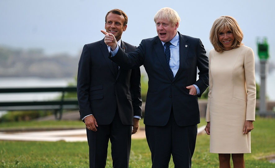 BIARRITZ, FRANCE - AUGUST 24: French President Emmanuel Macron (L), his wife Brigitte Macron (R) and British Prime Minister Boris Johnson pose for a photograph as they arrive for the G7 summit on August 24, 2019 in Biarritz, France. The French southwestern seaside resort of Biarritz is hosting the 45th G7 summit from August 24 to 26. High on the agenda will be the climate emergency, the US-China trade war, Britain's departure from the EU, and emergency talks on the Amazon wildfire crisis. (Photo by Neil Hall - Pool/Getty Images)