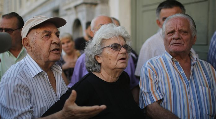 ATHENS, GREECE - JULY 07: Senior citizens talk to bank staff as they queue up to collect their pensions outside a National Bank of Greece branch in Kotzia Square on July 7, 2015 in Athens, Greece. Greek Prime Minister Alexis Tsipras is working on new debt crisis proposals and is due to present them at a Eurozone emergency summit today. (Photo by Christopher Furlong/Getty Images)